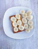 Banany i ciastka na białym porcelana talerzu Obrazy Stock