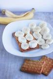 Banany i ciastka na porcelana talerzu Zdjęcia Royalty Free