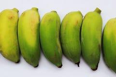 Banany które iść gotującym są zielonawym kolorem żółtym na whi Fotografia Stock