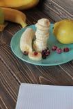 Banany są rżniętymi kubkami i zamarzniętym czerwonym jagodą obraz royalty free