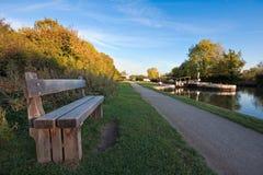 Banc à côté d'un towpath de canal en automne photo stock