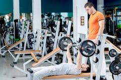 Banc à presse Deux athlètes occupés dans la salle de simulateur Un vous Photos stock