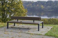 Banc avec les feuilles de chute et le backround d'automne - image courante Photos stock