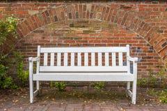 Banc blanc devant le mur de briques rouge, enchaîné au plancher Photographie stock