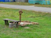 Banc bon et en bois de vieux fer rouillé parmi l'herbe verte photo stock