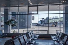 Banc dans le terminal d'aéroport et l'avion garé Images libres de droits