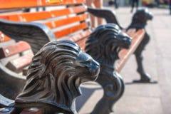 Banc de parc avec des jambes de fonte sous forme de tête d'un lion Image stock