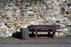 Banc de parc devant le mur en pierre de champ photos stock