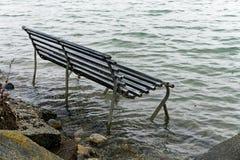 Banc de parc inondé par un niveau de la mer en hausse images stock