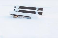 Banc de parc pendant un hiver froid couvert de tonnes de neige Photographie stock libre de droits