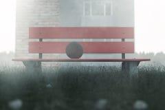Banc de parc rouge abandonné avec la boule là-dessus Photos stock