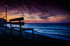 Banc de parc sur le rivage de coucher du soleil photo stock