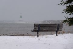 Banc de parc sur les rivages couverts par neige du lac Supérieur Images stock