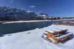 Banc de pique-nique couvert par la neige par la rivière d'arc en Alberta Foothills Canadian Rockies images stock
