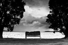 Banc de stationnement à la plage le jour orageux photos stock