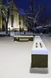 Banc de stationnement de neige de l'hiver par la cour Sibiu d'église de nuit Images stock