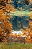 Banc de stationnement par Lake en automne Photographie stock