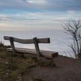 Banc en bois au-dessus de brouillard d'inversion dans la forêt noire Images libres de droits