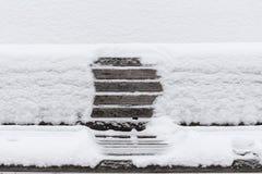 banc en bois couvert de neige avec une empreinte de quelqu'un Image libre de droits