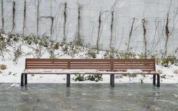 Banc en bois dans la neige au parc pendant l'hiver images stock