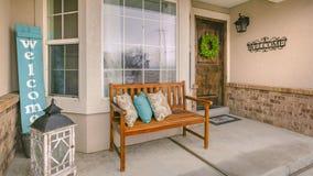 Banc en bois de porche de cadre de panorama avec des oreillers contre la fen?tre avant brillante photo stock