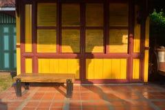 Banc en bois de vieux cru avec le mur en bois antique, maison thaïlandaise images stock