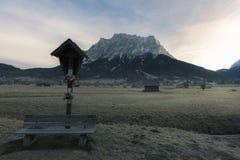 Banc en bois et croix sur un pré givré photographie stock