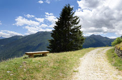 Banc en bois le long d'une route sinueuse Image stock