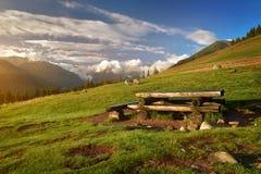 Banc en bois sur un pré de montagne de Tatra au surise Photographie stock