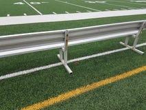 Banc en métal sur le terrain de football avec l'embouchure rouge photos libres de droits