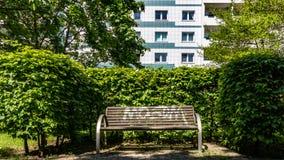 Banc en parc des bâtiments résidentiels Photographie stock libre de droits