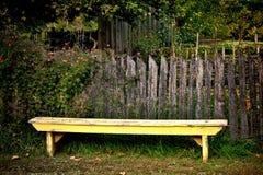 Banc jaune antique de jardin et vieille barrière de vintage Photo libre de droits