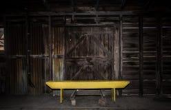 Banc jaune lumineux contre les portes de grange en bois image stock