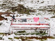 Banc neigeux rouge abandonné avec des poteaux et des vêtements de gel Images libres de droits