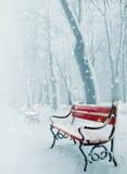 Banc rouge dans la neige Images libres de droits