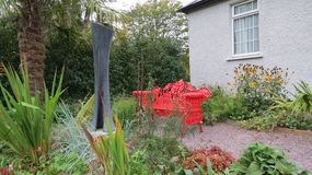 Banc rouge dans un jardin Photos stock