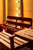 Banc rouge en bois et une table au café extérieur couvert de neige pendant l'hiver image libre de droits