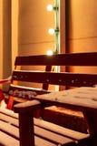 Banc rouge en bois et une table au café extérieur couvert de neige pendant l'hiver image stock