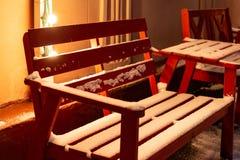Banc rouge en bois et une table au café extérieur couvert de neige pendant l'hiver images libres de droits