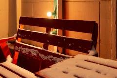 Banc rouge en bois et une table au café extérieur couvert de neige pendant l'hiver photos stock