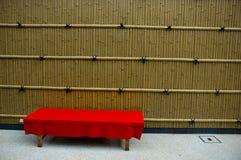 Banc rouge sur le bambou Photo stock
