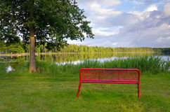Banc rouge sur une côte de lac Images libres de droits