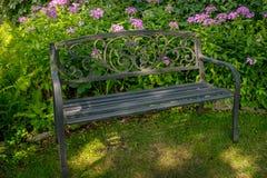 Banc se reposant placé dans un jardin avec des fleurs Photographie stock libre de droits