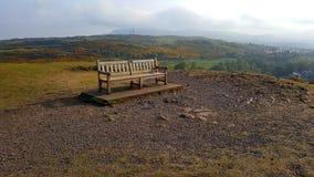 Banc sur le dessus d'une colline avec des nuages à l'arrière-plan Photographie stock libre de droits