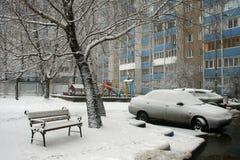 Banc, une voiture et un arbre couverts de neige Image libre de droits