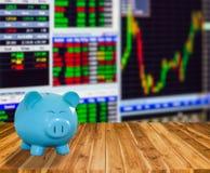 Banca blu del maiale su fondo di legno con il backgrou del mercato azionario della sfuocatura Fotografia Stock