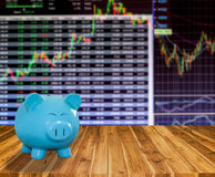 Banca blu del maiale su fondo di legno con il backgrou del mercato azionario della sfuocatura Immagini Stock Libere da Diritti