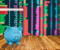 Banca blu del maiale su fondo di legno con il backgrou del mercato azionario della sfuocatura Fotografie Stock Libere da Diritti