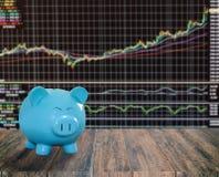 Banca blu del maiale su fondo di legno con il backgrou del mercato azionario della sfuocatura Fotografie Stock