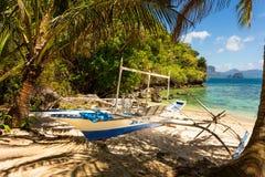 Banca boat at a beautiful tropical beach in Palawan Island,Phili. Traditional banca boat in the shade on the beach near Cudugnon Cave, El Nido, Palawan Island Stock Photos